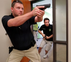 In this July 21, 2019 photo, Trainees Chris Graves, left, and Bryan Hetherington, right, participate in a security training session at Fellowship of the Parks campus in Haslet, Texas. (AP Photo/Tony Gutierrez)