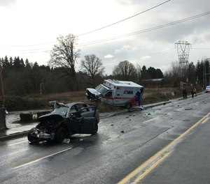 A vehicle collided with an AMR ambulance in Clark County, Washington, on Tuesday, injuring two paramedics and killing the other driver, officials said.