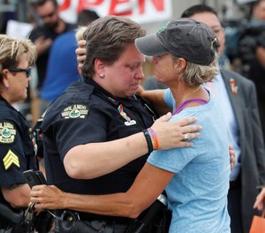 In this June 12, 2017 file photo, Orlando police department Officer Alison Clarke is embraced by Christine Gogicos while visiting the memorial outside the Pulse Nightclub on the one-year anniversary of the shooting in Orlando. (Photo/TNS)