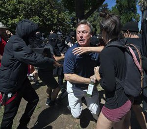 KCRA television reporter Mike Luery runs away from members of the group called ANTIFA Sacramento (Anti-Fascism Action), at the California state Capitol in Sacramento, Calif., Sunday, June 26, 2016. (Paul Kitagaki Jr./The Sacramento Bee via AP)