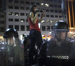 A protestor films riot police as they advance on a small march against the acquittal of Michael Brelo, Saturday, May 23, 2015.
