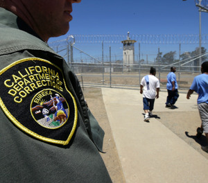 In this June 20, 2018 file photo , inmates pass a correctional officer as they leave an exercise yard at the California Medical Facility in Vacaville, Calif.