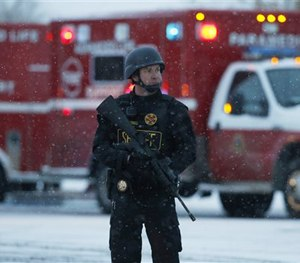 An officer stands guard near a Planned Parenthood clinic Friday, Nov. 27, 2015, in Colorado Springs, Colo. (AP Image)