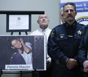 A photograph of Pamela Maurer is displayed as law enforcement officials listen to DuPage County State's Attorney Robert Berlin (not pictured) speak at a news conference regarding her 1976 slaying. (Photo/TNS)