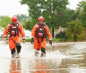 Mountain View Fire Rescue department firefighters Jamie Wood and Steve Knoll walk through a food of water after doing a welfare check of a flooded property in rural Erie, Colo. on Thursday, Sept. 12, 2013.
