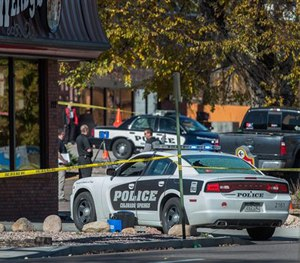 The rear window of a Colorado Springs Police car is shattered after a shooting Saturday, Oct. 31, 2015, in Colorado Springs, Colo. (Christian Murdock/The Gazette via AP)