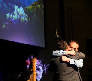 Tom Tonelli, facing camera, a teacher at Columbine High School, hugs former principal Frank DeAngelis during a faith-based memorial service for the victims of the school nearly 20 years earlier, at a community church, Thursday, April 18, 2019, in Littleton, Colo.