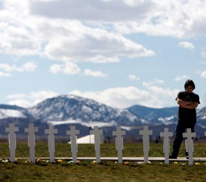 Garrett Bentley looks at a display of crosses for the 13 victims of the massacre at Columbine High School to mark the 10th anniversary of the killings near the Columbine Memorial in the southwest Denver suburb of Littleton, Colo., on Monday, April 20, 2009.