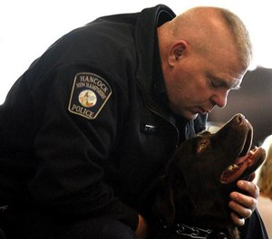 Chief Andrew Wood of the Hancock Police Department interacts with his department's comfort dog, Rookie. (Photo/TNS)