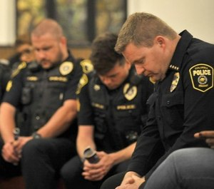 Columbus Police Chief Geoff Jones (right) prays with officers and church members at the Second Baptist Church. Jones has been working with the city to implement a series of community-based policing policies. (Photo/TNS)