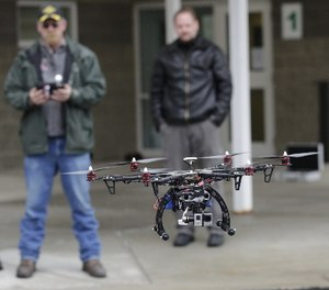 In this Feb. 13, 2014, photo, members of the Box Elder County Sheriff's Office search and rescue team fly their search and rescue drone during a demonstration, in Brigham City, Utah.
