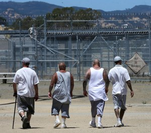 In this photo taken June 20, 2018, inmates walk the exercise yard at the California Medical Facility in Vacaville, Calif. (AP Photo/Rich Pedroncelli)