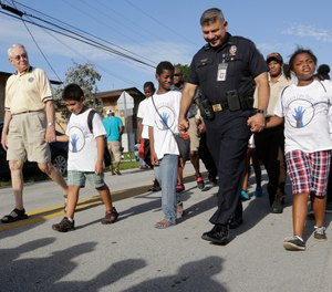 Children walk hand in hand with police during a peace march, Friday, Aug. 19, 2016, in the Liberty City neighborhood of Miami. Various police departments from across Miami-Dade County marched with neighborhood children to promote community relations between residents and police. (AP Photo/Lynne Sladky)