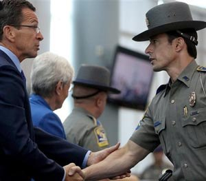 Connecticut Gov. Dannel P. Malloy, left, shakes the hand of State Police detective Thomas Kiely during a ceremony honoring responders to the Sandy Hook Elementary School shooting in December 2012 at Rentschler Field in East Hartford Conn., Tuesday July 8, 2014.