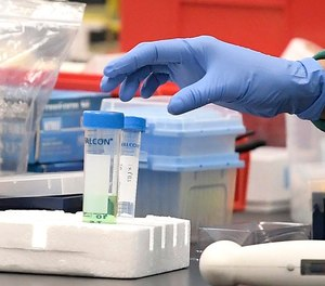 A researcher at Protein Sciences reaches for a vial in a lab, Thursday, March 12, 2020, in Meriden, Conn. The biotech company is currently researching a vaccine for COVID-19.