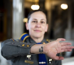 Trooper Christine Jeltema shows tattoos that memorialize her deployments to Eastern Europe and Iraq when she was a soldier with the U.S. Army.