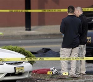 A person lays on the ground near evidence markers as officials investigate the scene where a Jersey City Police Department officer was shot and killed while responding to a call at a 24-hour pharmacy, Sunday, July 13, 2014, in Jersey City, N.J. (AP Image)