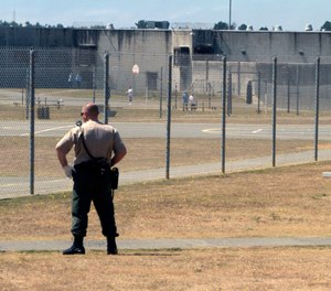 In this Aug. 17, 2011 file photo, a correctional officer keeps watch on inmates in the recreation yard at Pelican Bay State Prison near Crescent City, Calif. (AP Photo/Rich Pedroncelli)