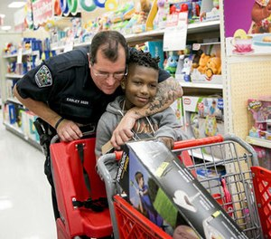 In this Dec. 15, 2016 file photo, Austin Police officer David Easley puts a tattooed arm around Jarvis Moblin, 8, in a hug during the 14th annual Shop With A Cop shopping spree at a Target in Austin, Texas.