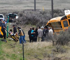 Emergency personnel help to remove passengers from the school bus. (Drew Nash/The Times-News via AP)