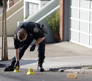 A San Francisco Police officer places a marker on the street after shootings in San Francisco, Wednesday, Nov. 1, 2017.