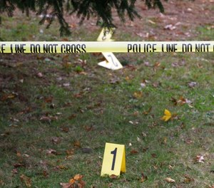 Evidence markers are visible behind police crime scene tape in Weymouth, Mass., Friday morning, Nov. 11, 2011. (AP Photo/Stephan Savoia)