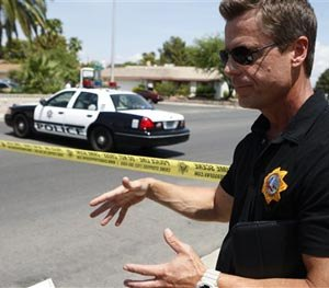 Las Vegas police Sgt. John Sheahan speaks to the media at the scene of a home invasion and shooting in Las Vegas on Tuesday, July 29, 2014. (AP Image)