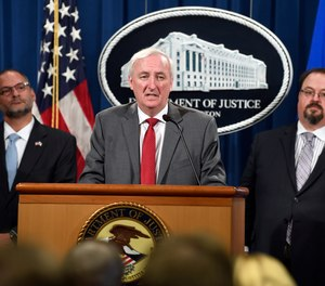 Deputy Attorney General Jeffrey Rosen, center, flanked by Hugh Hurwitz, left, the acting director of the Bureau of Prisons, and David Muhlhausen, director of the National Institute of Justice, speaks during a news conference at the Justice Department in Washington, Friday, July 19, 2019, on developments in the implementation of the First Step Act.