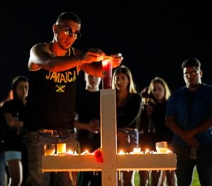 Joey Kandil, 18, a recent graduate of Marjory Stoneman Douglas High School, places a ring around a candle on one of seventeen crosses, after a candlelight vigil for the victims of the Wednesday shooting at the school, in Parkland, Fla., Thursday, Feb. 15, 2018. (AP Photo/Gerald Herbert)