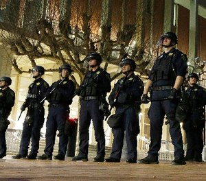 In this Feb. 1, 2017 file photo, University of California, Berkeley police guard the building where Breitbart News editor Milo Yiannopoulos was to speak. (AP Photo/Ben Margot, File)