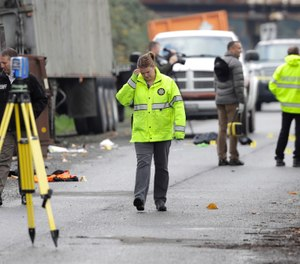 King Co. Sheriff's Dept. investigators walk near the scene of a shooting, Wednesday, Nov. 7, 2018, near a scrap metal yard in Kent, Wash. (AP Photo/Ted S. Warren)