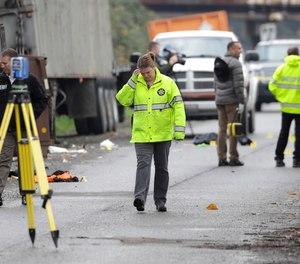 King Co. Sheriff's Dept. investigators walk near the scene of a shooting, Wednesday, Nov. 7, 2018, near a scrap metal yard in Kent, Wash.