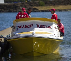 Honolulu Fire Department search and rescue members sit on a docked boat at a boat harbor. (Photo/AP)
