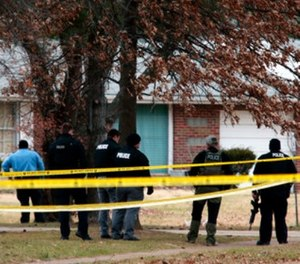Police officers work the scene where two St. Louis County officers were shot and a man barricaded himself inside a home on Thursday, Dec. 14, 2017, in the St. Louis County town of Bellefontaine Neighbors, Mo.