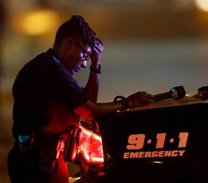 In this July 8, 2016, file photo, a Dallas police officer, who did not want to be identified, takes a moment as she guards an intersection in the early morning after a shooting in downtown Dallas.