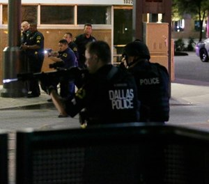 In this July 7, 2016, file photo, Dallas police move to detain a driver after several police officers were shot in downtown Dallas.