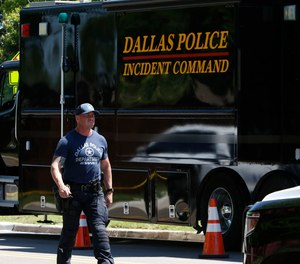 A Dallas SWAT officer walks near the scene of home on Highcrest Drive after a domestic violence call-turned-murder-suicide early Monday morning on May 18, 2020.