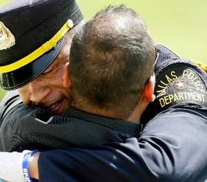 A Dallas police officer gets a hug after an honor guard ceremony for Dallas police officer Patrick Zamarripa at Dallas-Fort Worth National Cemetery in Dallas, Saturday, July 16, 2016.