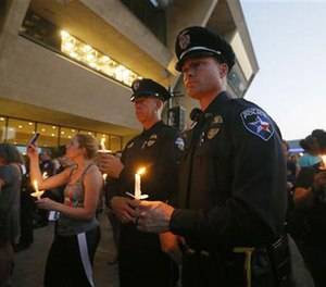 Police officers take part in a candlelight vigil at City Hall, Monday, July 11, 2016, in Dallas. Five police officers were killed and several injured during a shooting in downtown Dallas last Thursday night. (AP Photo/Tony Gutierrez)