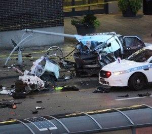Dayton police work the scene of a crash on East Third Street involving a stolen Riverside police SUV in Dayton, Ohio, Tuesday, Aug. 27, 2019. (Amelia Robinson/Dayton Daily News via AP)