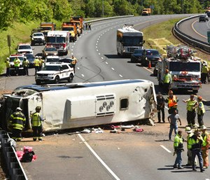 Emergency workers tend to an overturned bus on I-95 southbound. (Amy Davis/The Baltimore Sun via AP)