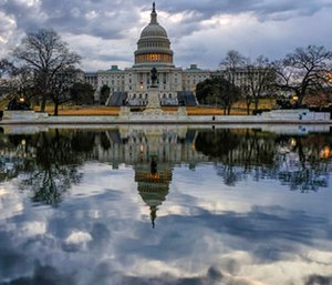 Clouds are reflected in the U.S. Capitol reflecting pool at daybreak in Washington as Day Three of the government shutdown continues, Monday, Jan. 22, 2018.