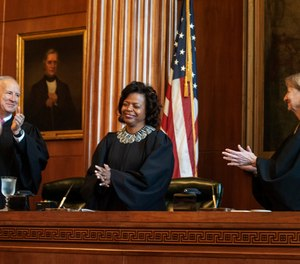 In this March 7, 2019, file photo, Associate Justices Paul Newby, left, and Robin Hudson, right, applaud for new Chief Justice Cheri Beasley of the N.C. Supreme Court during Beasley's investiture ceremony in Raleigh, N.C. (Paul Woolverton/The Fayetteville Observer via AP, File)