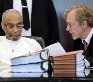 This Aug. 28, 2019, file photo shows Abu-Ali Abdur'Rahman, left, signing a court order with the help of his attorney, Brad MacLean, right, during a hearing in Nashville, Tenn. (AP Photo/Mark Humphrey, File)