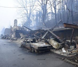 A structure and vehicle are damaged from the wildfires around Gatlinburg, Tenn., on Tuesday, Nov. 29, 2016. (Michael Patrick/Knoxville News Sentinel via AP)