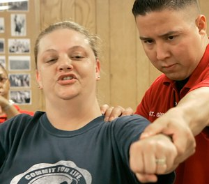 Texas Department of Criminal Justice Sgt. Louis Garcia, right, works with corrections officer trainee Christy Lawson on her jabs during a training session at the Minnie Houston Training Center in Riverside, Texas, Thursday, May 3, 2007.