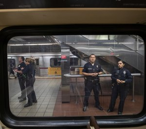 LAPD officers stand guard inside the 7th St/Metro Center subway station in Los Angeles, Calif., on March 26, 2020. (Photo/Brian van der Brug/Los Angeles Times)