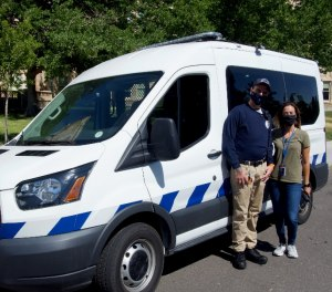 Two civilian health care workers with Denver's Support Team Assisted Response program pose with their van.