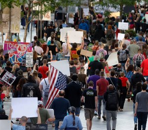Protesters walk down the 16th Street mall during a protest over the death of George Floyd, a handcuffed black man who died in police custody in Minneapolis, Thursday, May 28, 2020, in Denver. (AP Photo/David Zalubowski)