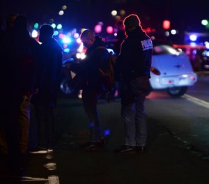 Detroit Police officers gather where one officer was fatally shot and another was wounded while responding to a home invasion on Detroit's West Side, late Wednesday night. (Photo/AP)